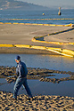 A man walks by the beach at Crissy Field wreathed in oil spill containment booms. On November 7, 2007 the Cosco Busan container ship spilled an estimated 58,000 gallons of bunker fuel into San Francisco Bay after striking a tower of the San Francisco-Oakland Bay Bridge.
