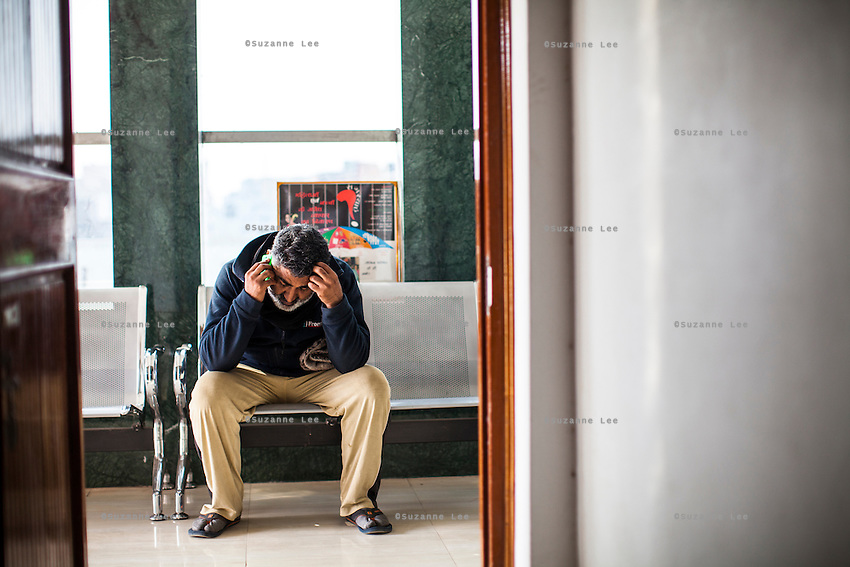 Ajeet Singh, founder of Guria Swayam Sevi Sansthan, rests on a bench as he speaks on the phone after a long week of working on a case with Guria's lawyers, in the Guria office in Varanasi, Uttar Pradesh, India on 25 November 2013.