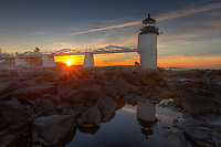 Marshall Point Lighthouse and its reflection in a tidal pool at sunrise in Port Clyde, Maine.