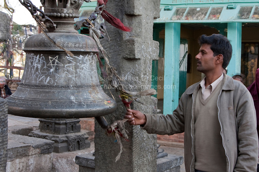 Kathmandu, Nepal.  Nepali Worshipper Rings a Bell at Swayambhunath Temple.  Bells drive evil spirits away.