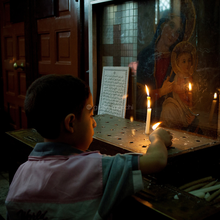Egypt / Cairo / 15.4.2012 / A young boy lights a candle during the Coptic Easter in a church in Shubra, an area in the North of Cairo now heavily populated, with an estimated three million residents, including a large Coptic population. Shubra has the highest concentration of Copts in Cairo.