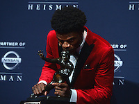 New York, NY - December 10, 2016: After winning the 2016 Heisman Trophy, Louisville quarterback Lamar Jackson kisses his trophy during a news conference at the New York Marriott Marquis, December 10, 2016. At the time Jackson won the Heisman, he has a total of 4,928 offensive yards, 2nd of all-time for a Heisman winner. (Photo by Don Baxter/Media Images International)