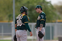 Oakland Athletics relief pitcher Dakota Chalmers (50) talks to catcher Santiago Chavez (66) during a Minor League Spring Training game against the Chicago Cubs at Sloan Park on March 13, 2018 in Mesa, Arizona. (Zachary Lucy/Four Seam Images)