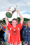 East Kerry captain James McCarrick holds up the minor championship trophy in Killorglin on Saturday.