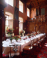 The table is laid for a formal dinner in this double-height wood-panelled dining room