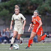 Boston College midfielder Kristen Mewis (19) on the attack as University of Miami midfielder Erin McGovern (13) closes..After two overtime periods, Boston College (gold) tied University of Miami (orange), 0-0, at Newton Campus Field, October 21, 2012.