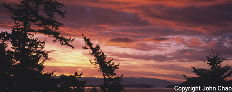 Sunrise rays break the sky over Rosario Strait in the San Juan Island, Washington State. Taken from Orcas Island in panoramic format.