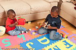 12 month old baby boy sitting on floor playing  with toy blocks and container while older brother age 3 plays game with toy animals horizontal