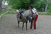 Shetland-Pony, Shetlandpony, Shetty, Shetti, Ponyhof, Shetland - Pony wird eingeritten, Mädchen, Kind legt sich zunächst auf den Sattel, Reitlehrerin hilft, Reiten