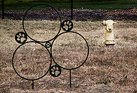 Features at a neighborhood dog park include a metal fixture with hoops and decorative paw prints as well as the ever present fire hydrant.