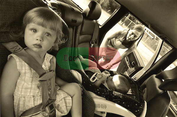 5 year old girl in child car seat while mother buckles infant sibling into baby seat on other side, parenting