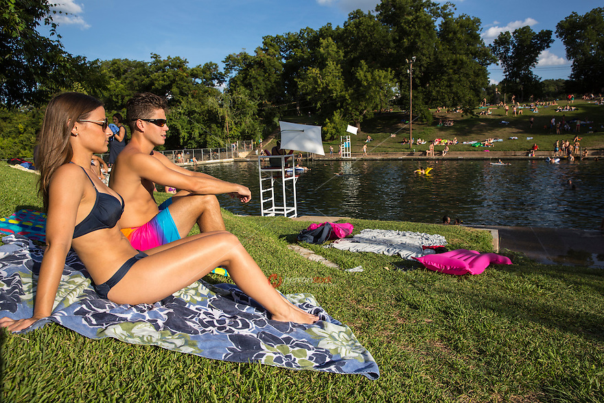 """Young attractive male and female couple sunbath at Barton Springs Pool. Visitors can swim in the constant 68-degree waters of Barton Springs Pool, a spring-fed swimming hole in Zilker Park. Voted the """"Best Swimming Hole in Texas."""""""