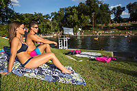 "Young attractive male and female couple sunbath at Barton Springs Pool. Visitors can swim in the constant 68-degree waters of Barton Springs Pool, a spring-fed swimming hole in Zilker Park. Voted the ""Best Swimming Hole in Texas."""