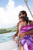 FRENCH POLYNESIA, Raiatea Island. Grandmother and her grandchild on a boat heading towards Raiatea Island.