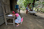 Sindy Kelly Saraiva, 4, does her first grade homework outside her home in the countryside near Anapu, in Brazil's northern Para State. In the background, her mother, Fabiana do Nacimiento, prepares food. This area was forest land until recent decades, when the expansion of the agrarian frontier led to the steady destruction of this part of the Amazon's rain forest. <br /> <br /> Parental consent obtained.
