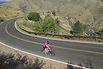 Woman biking up Lookout Mountain west of Denver, Colorado, USA. .  John offers private photo tours in Denver, Boulder and throughout Colorado. Year-round.