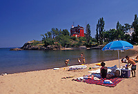 AJ2835, beach, Lake Superior, Upper Peninsula, U.P., Michigan, People enjoying a day in the sun at Shiras Park Beach with red lighthouse and coast guard station in the distance on Lake Superior in Marquette in the state of Michigan.