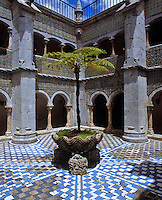 A young palm tree stands in the centre of the Manueline cloisters surrounded by 6th century Mudejar tiles