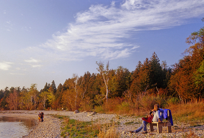 A couple relaxes on a bench and enjoys a warm fall afternoon on the Peninsula State Park, Green Bay shoreline, Door County, Wisconsin.