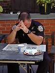 A police officer hangs his head as he readds the news about Grund Zero three days after the attack.