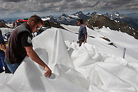 Mountains of fleece blanet are unraveled to cover Brunnenkogel Ferner (Austrian word for glacier).  It is wrapped  to keep it from melting.  Covered ice melts slower. <br /> The ski area at 3,400 meters is covered to help save the ski industry since the glacier is retreating.  The cost of materials is one Euro per square meter.<br /> <br /> The Alpine glaciers -- in Austria, Switzerland, France and Italy -- are losing one percent of their mass every year and, even supposing no acceleration in that rate, will have all but disappeared by the end of the century.