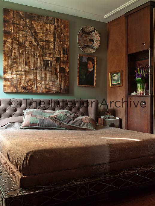 The guest bedroom features a leather bedframe and above the bed is a work by Canan Tolon. The patchwork pillows are Ralph Lauren