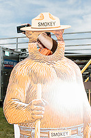 A campaign worker is seen behind a Smokey the Bear photo cutout as Kentucky senator and Republican presidential candidate Rand Paul meets people during his campaign stop at the North Haverhill Fair in North Haverhill, New Hampshire.