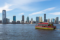A NY Waterway ferry departs the World Financial Center Ferry Terminal, with the skyline of Jersey City in the background across the Hudson River.