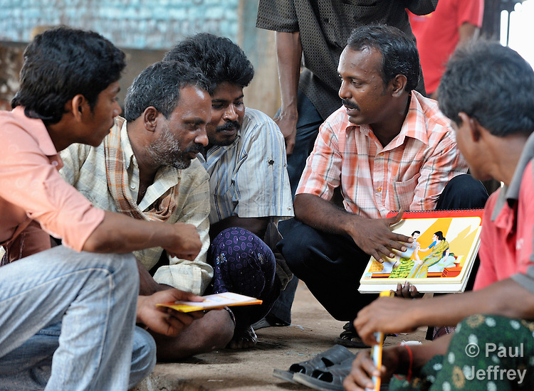 Simon Charles, an educator with the Madras Christian Council of Social Service, meets with fisherfolk at the dock in Chennai, India, to explain HIV and AIDS and how HIV can be transmitted.