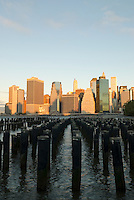 AVAILABLE FROM GETTY IMAGES FOR LICENSING.  Please go to www.gettyimages.com and search for image # 141112702.<br /> <br /> <br /> Lower Manhattan Financial District Skyline in the Early Morning Light, with Wooden Posts in the East River in the Foreground, New York City, New York State, USA