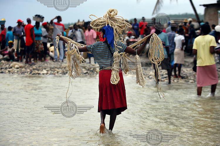 A woman seels spliced rope in the flooded market place in Bainet. The flooding is due to Hurricane Dean.