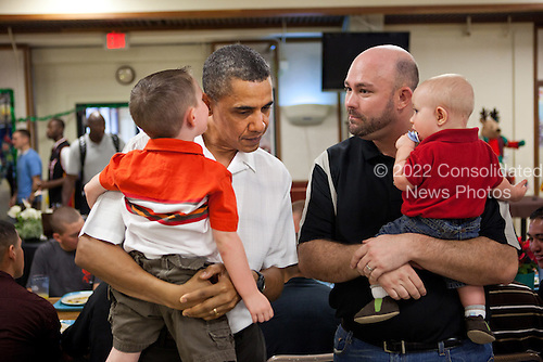 United States President Barack Obama listens as a child whispers in his ear during Christmas dinner in the mess hall at Marine Corps Base Hawaii in Kailua, Hawaii, December 25, 2010..Mandatory Credit: Pete Souza - White House via CNP