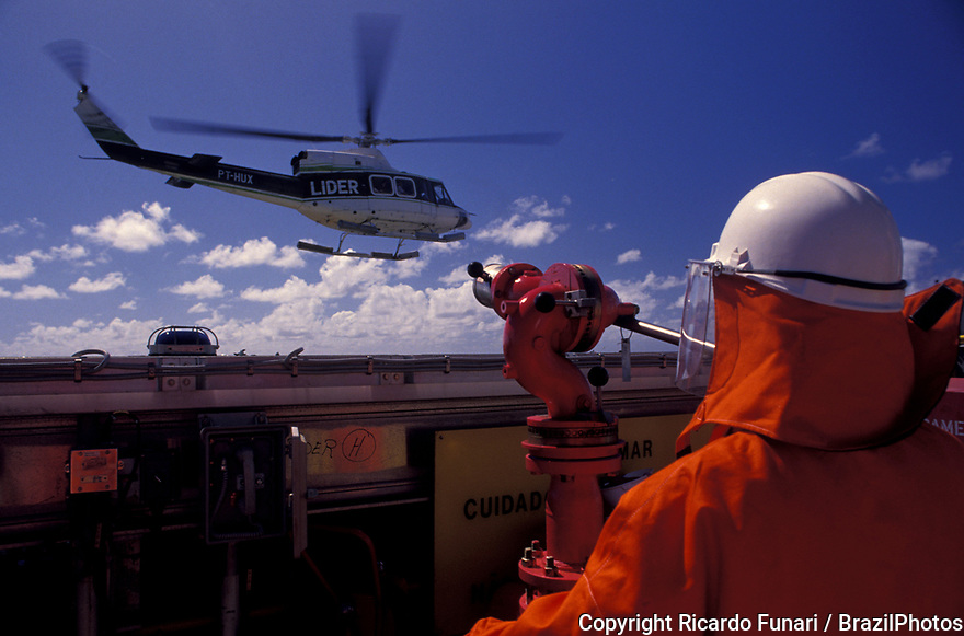 Fire extinguisher, fire prevention operation during helicopter landing at petroleum platform worker in Brazil.