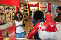 """ADDIS ABABA, ETHIOPIA - NOVEMBER 13: A young women tries a pair of red Prada sunglasses at the """"Lady Shop"""" an up-market clothing shop for women on November 13, 2010 in a shopping mall in Addis Ababa, Ethiopia. Some people can afford to buy expensive locally  and imported cloths despite that this one of Africa's poorest countries. (Photo by Per-Anders Pettersson)"""