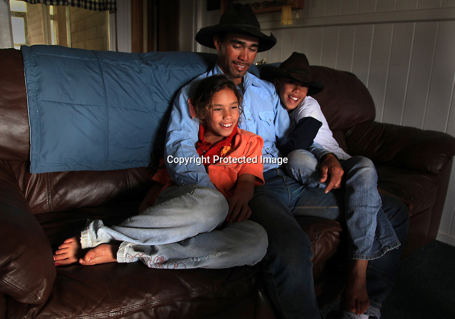 "WayneTachera and his daughters, Nahe, 9, and Kamehana, 11, are photographed at their home on Kahua Ranch in North Kohala, Hawaii. The house is part of ""cowboy housing"" which is subsidized by the ranch as part of a cowboy's benefit package. ""We get free housing, free electricity, free water.  It makes up for cowboy pay because cowboy pay is not much at all"","" says Tachera.  Nahe and her sister, Kamehana, are very close to their father who taught them to ride horses as toddlers and took them to work with him when childcare wasn't available."