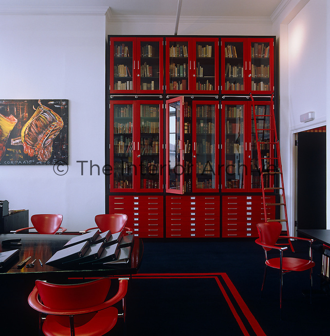 A red lacquer glass-fronted bookcase has a sliding ladder which provides access to the top shelves in this contemporary home office