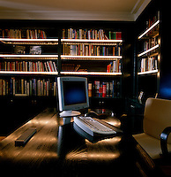 Subtle strip lighting lines the shelves in this library-cum-study creating an intimate and masculine space