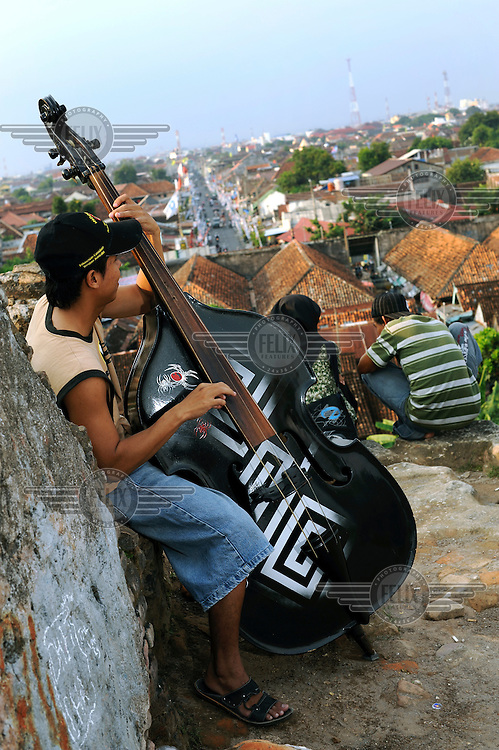 A man plays a double-bass on the ramparts of an old building that over-looks central Yogyakarta.