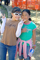 Smiling fashionably dressed Hmong teenagers giving the peace sign. Hmong Sports Festival McMurray Field St Paul Minnesota USA