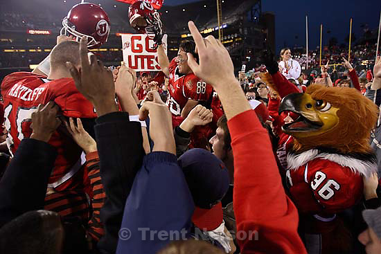 Utah quarterback Brett Ratliff and Travis LaTendresse (right) are lifted up by fans after the win. University of Utah vs. Georgia Tech, Emerald Bowl, San Francisco.<br />