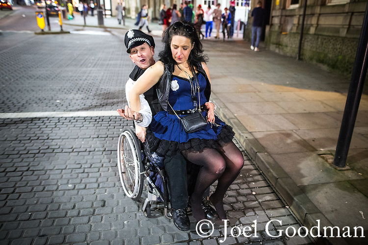 © Joel Goodman - 07973 332324 . 27/12/2015 . Wigan , UK . A wheelchair user gives a ride to a woman who has fallen on the pavement and cut her lip . Revellers in Wigan enjoy Boxing Day drinks and clubbing in Wigan Wallgate . In recent years a tradition has been established in which put on fancy dress for a Boxing Day night out . Photo credit : Joel Goodman