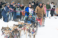 Karin Hendrickson and team run past spectators on the bike/ski trail near University Lake with an Iditarider in the basket and a handler during the Anchorage, Alaska ceremonial start on Saturday, March 7 during the 2020 Iditarod race. Photo © 2020 by Ed Bennett/Bennett Images LLC