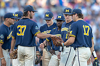 Michigan Wolverines pitcher Karl Kauffmann (37) hands Jeff Criswell (17) the ball against the Vanderbilt Commodores during Game 3 of the NCAA College World Series Finals on June 26, 2019 at TD Ameritrade Park in Omaha, Nebraska. Vanderbilt defeated Michigan 8-2 to win the National Championship. (Andrew Woolley/Four Seam Images)