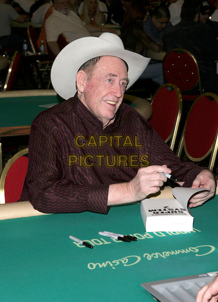 """DOYLE BRUNSON.Signs copies of his book """"Super System 2"""" held at Commerce Casino, USA, 17 February 2005..half length cowboy hat.Ref: ADM.www.capitalpictures.com.sales@capitalpictures.com.©Z.LippAdMedia/Capital Pictures ."""