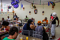 RIO DE JANEIRO, BRAZIL - FEBRUARY 22, 2014: Outpatients, take their lunch at the Pinel Instituto psychiatric hospital during a day of preparation for the annual T&aacute; Pirando, Pirado, Pirou! carnival street parade on February 22, 2014 in Rio De Janeiro, Brazil. It looks like any of the other 450 or so street parties, locally called &ldquo;carnival blocks,&rdquo; that parade through Rio de Janeiro during the raucous pre-Lenten festivities that draw hundreds of thousands to the city each year. What makes this party different are its performers and organizers: psychiatric patients and their doctors, therapists, family members, neighbors and passers-by. The group, called T&aacute; Pirando, Pirado, Pirou!, which roughly translates as &ldquo;We&rsquo;re freaking out, we already freaked out!&rdquo;, began ten years ago when Brazil was in the process of dismantling its century-old system of mental asylums. A law passed in 2001 called for long-term outpatient psychiatric care to be offered primarily in community clinics. The number of such clinics increased more than fivefold in the following decade, while the number of asylum beds for psychiatric patients dropped 40 percent nationwide.<br /> <br /> Daniel Berehulak for The New York Times