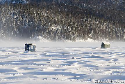 Ice fishing huts on a windy frozen lake