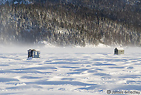 Ice fishing huts on a windy frozen lake