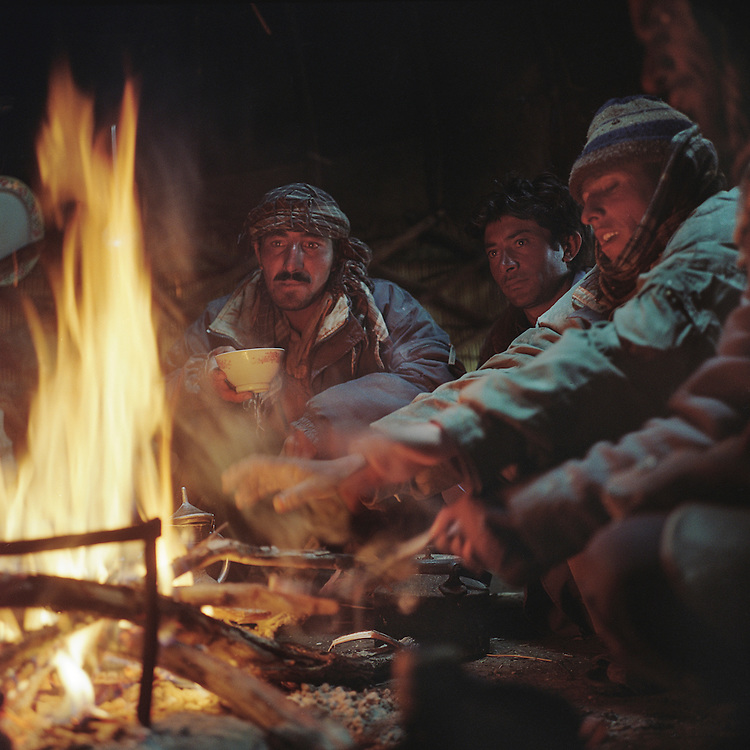 Wakhi shepherds and horsemen warm themselves by a fire in their yurt in the Big Pamir Mountains after a bringing in their sheep, goats, yaks and horses for the evening.