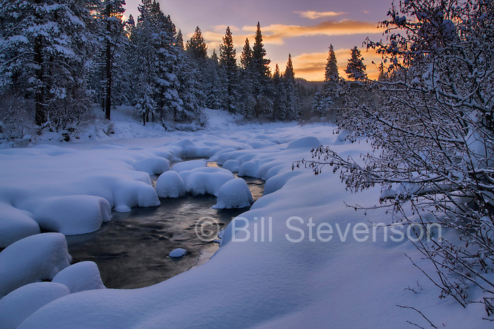 A picture of the Truckee River at sunrise in winter with snow