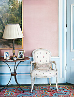 A vibrant geometrically patterned carpet complements the pale blue and pink walls of this sitting room